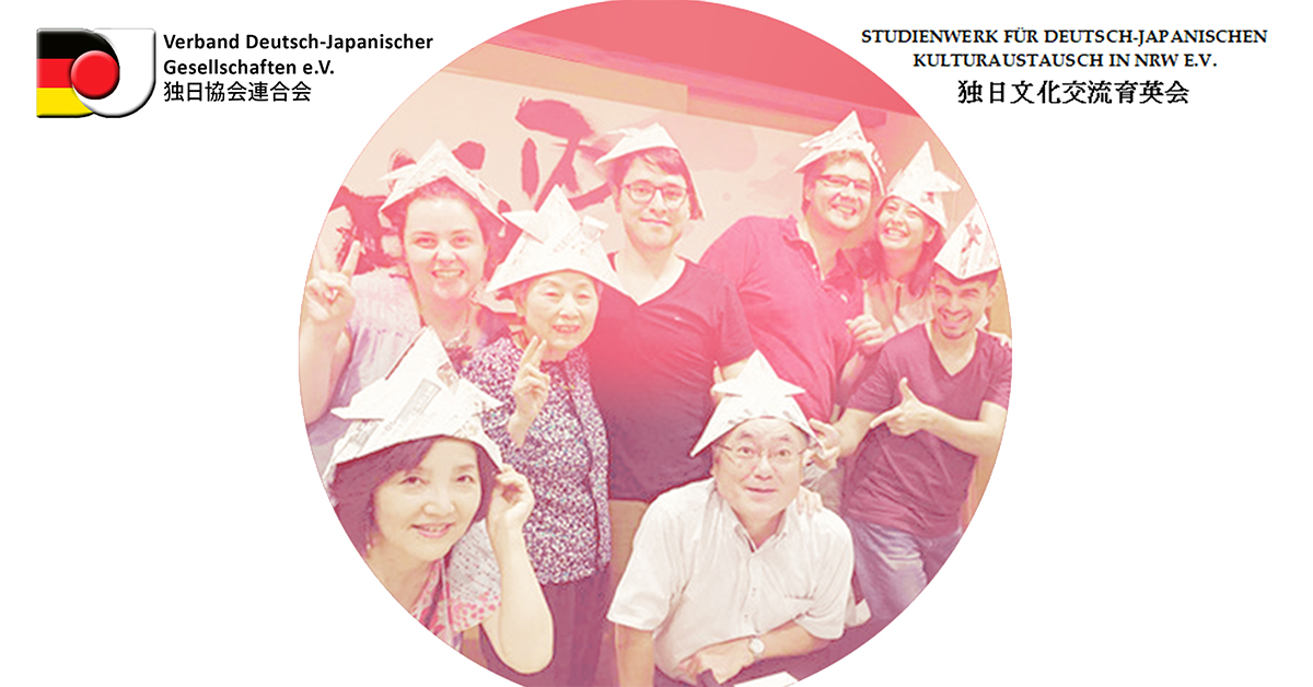 Foto: Gruppenbild von Japanern und Deutschen mit gebastelten Papierhüten